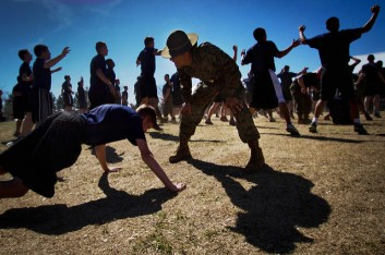 Boot camp drill instructor yelling at someone doing push ups